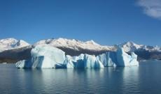Blue glacial iceberg floating along the coast